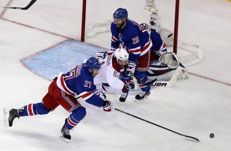 May 29, 2014; New York, NY, USA; Montreal Canadiens center David Desharnais (51) chases the puck against New York Rangers defenseman Ryan McDonagh (27) and center Dominic Moore (28) during the third period in game six of the Eastern Conference Final of the 2014 Stanley Cup Playoffs at Madison Square Garden. Mandatory Credit: Adam Hunger-USA TODAY Sports