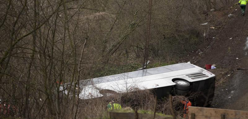 A Polish bus lies on its side after it crashed down a ravine in Ranst, Belgium on Sunday, April 14, 2013. The bus carrying Russian youngsters crashed through guardrails and off a highway onto a field below near the port city of Antwerp on Sunday, killing at least five people and leaving five more critically injured. (AP Photo/Virginia Mayo)