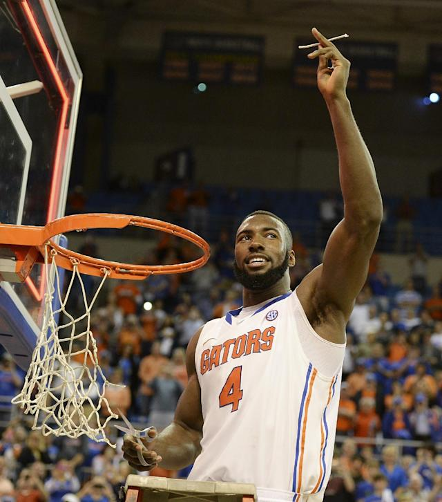 Florida's Patric Young holds up a piece of the net after the Gators became the first team in Southeastern Conference history to go 18-0 in league play, Saturday, March 8, 2014 in Gainesville, Fla. Florida defeated Kentucky 84-65 Saturday in an NCAA college basketball game. (AP Photo/Phil Sandlin)