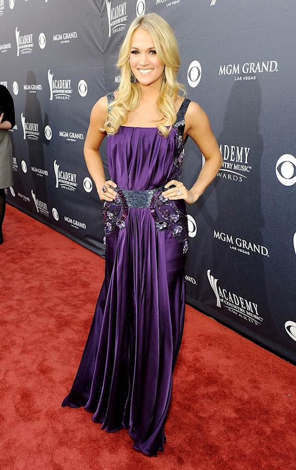 """Carrie Underwood  Grade: B+   Carrie Underwood -- who's also know for her impeccable sense of style -- picked a deep purple Jean Fares Couture frock for the occasion. While it didn't necessarily do her fab physique justice, Carrie still looked stunning. Frazer Harrison/ACMA2011/<a href=""""http://www.gettyimages.com/"""" target=""""new"""">GettyImages.com</a> - April 3, 2011"""