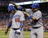 Los Angeles Dodgers' Adrian Gonzalez, right, and Yasiel Puig celebrate after both players scored on a single by Skip Schumaker during the second inning of a baseball game against the St. Louis Cardinals on Wednesday, Aug. 7, 2013, in St. Louis. (AP Photo/Jeff Roberson)