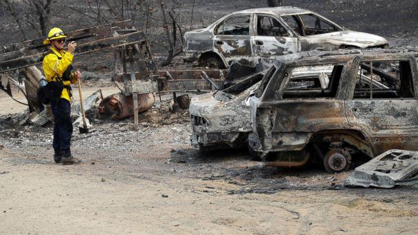 San Bernardino County Fire Department firefighter James Lippen takes photos of the damage caused by a wildfire, Sunday, July 29, 2018, in Keswick, Calif. (AP)
