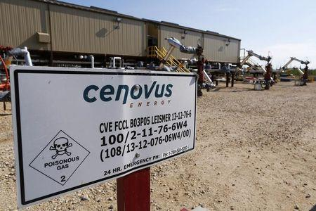 A warning sign is pictured near well heads that inject steam into the ground and pump oil out at the Cenovus Energy Christina Lake SAGD project south of Fort McMurray