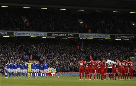 Oldham Athletic players (L) and Liverpool players stand during a minute's silence in honour of former Oldham Athletic and Liverpool player Wayne Harrison and Portuguese great Eusebio during their FA Cup third round soccer match at Anfield in Liverpool January 5, 2014. REUTERS/Phil Noble