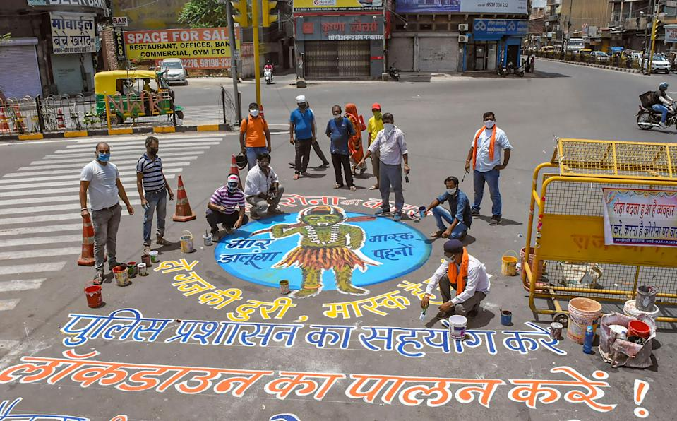 Artistes and activists paint a rangoli to create awareness on COVID-19, during the second wave of coronavirus pandemic in India, in Jodhpur, on Wednesday, 28 April 2021.