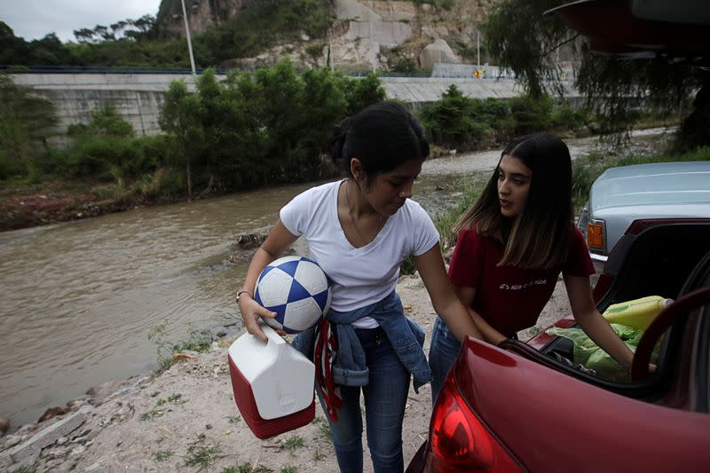 Residents arrange their belongings in the trunk of their car whilst evacuating their house in anticipation of heavy rains as Hurricane Iota approaches, in Tegucigalpa