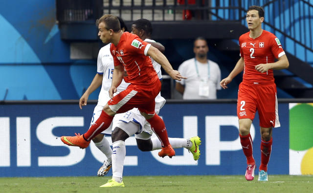 FILe - In this June 25, 2014 file photo, Switzerland's Xherdan Shaqiri, left, scores the opening goal during the group E World Cup soccer match between Honduras and Switzerland at the Arena da Amazonia in Manaus, Brazil. Shaqiri collected the ball outside the top right corner of the area, dribbled to avoid a pair of defenders and then launched a curling shot toward the top left corner of the net that went in off the underside of the crossbar. (AP Photo/Kirsty Wigglesworth, File)