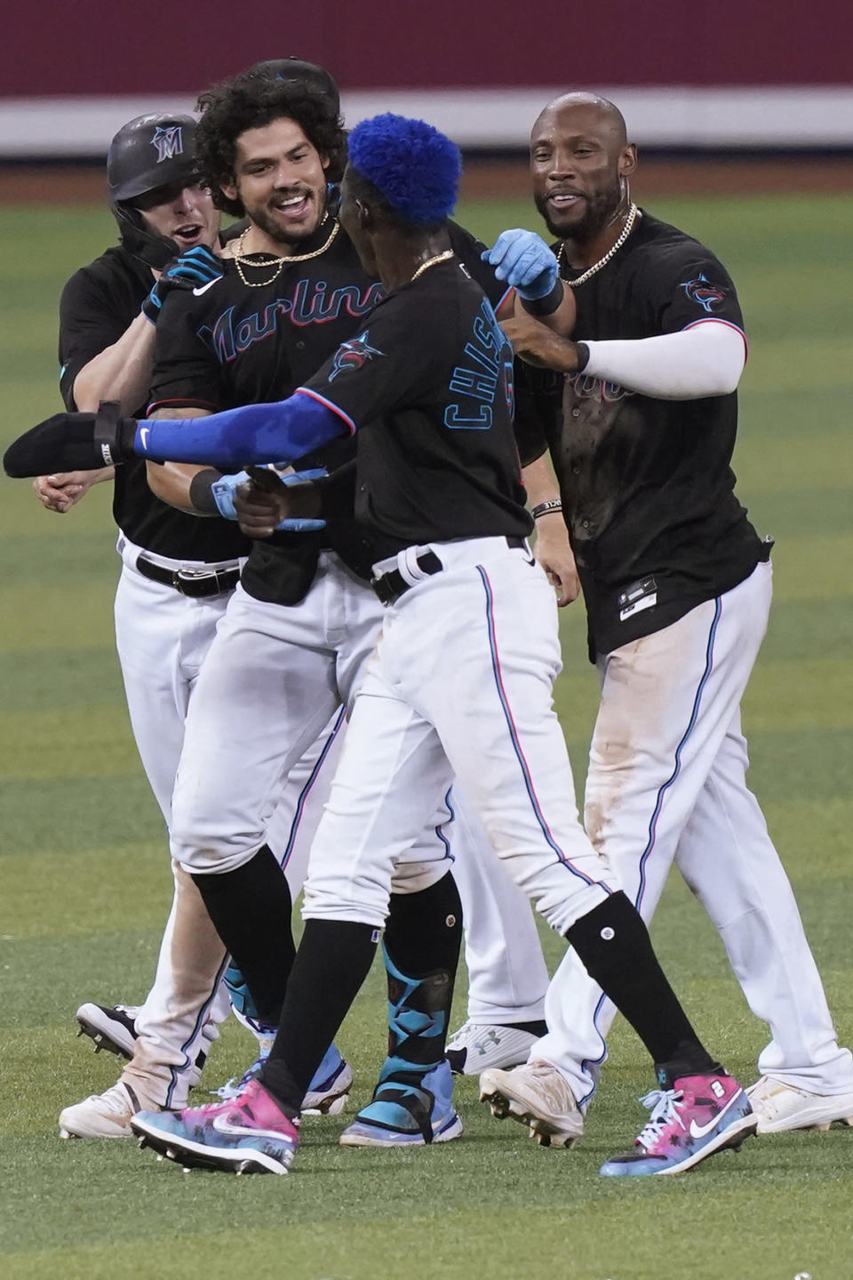 Miami Marlins' Jorge Alfaro, center, is congratulated after he hit a double to drive in the winning run in the 10th inning of the team's baseball game against the San Francisco Giants, Saturday, April 17, 2021, in Miami. The Marlins won 7-6. (AP Photo/Marta Lavandier)