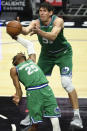Dallas Mavericks forward Wes Iwundu, left, and center Boban Marjanovic, right, reach for a rebound during the second half of an NBA basketball game against the Los Angeles Clippers in Los Angeles Sunday, Dec. 27, 2020. (AP Photo/Kyusung Gong)