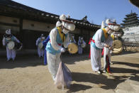 South Korean traditional band members wearing face masks as a precaution against the coronavirus pray during a ceremony to celebrate Jeongwol Daeboreum, or Great Full Moon Day, the first full moon of the Lunar New year, at the National Folk Museum of Korea in Seoul, South Korea, Friday, Feb. 26, 2021. (AP Photo/Ahn Young-joon)