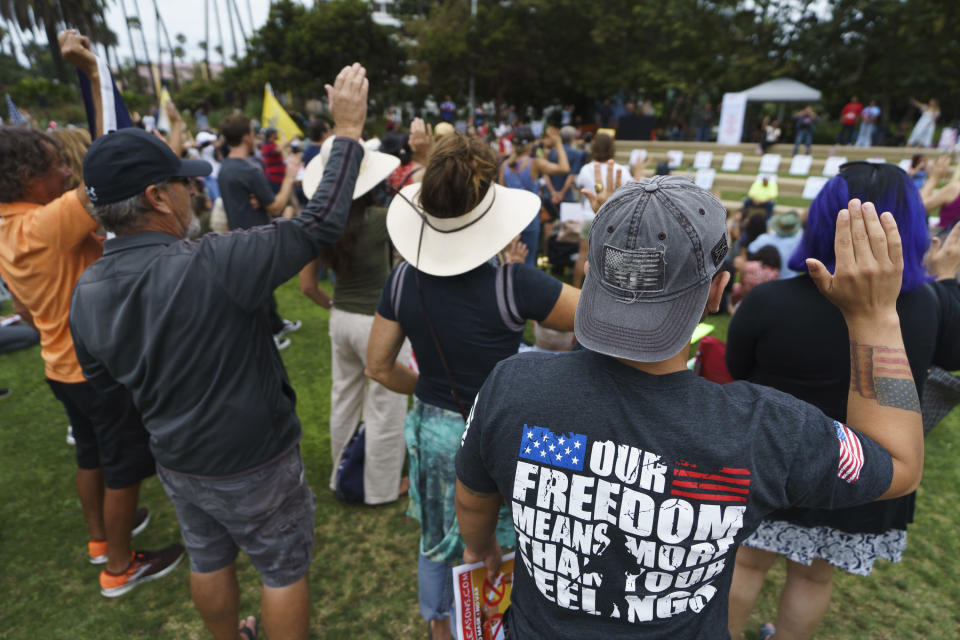 """People rise their right hand as they pledge at the """"S.O.S California No Vaccine Passport Rally"""" at Tongva Park in Santa Monica, Calif., Saturday, Aug. 21, 2021. (AP Photo/Damian Dovarganes)"""
