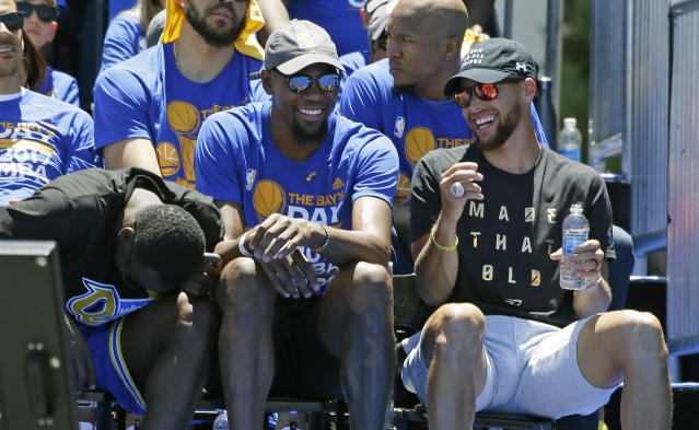 """<a class=""""link rapid-noclick-resp"""" href=""""/nba/players/4244/"""" data-ylk=""""slk:Kevin Durant"""">Kevin Durant</a> and <a class=""""link rapid-noclick-resp"""" href=""""/nba/players/4612/"""" data-ylk=""""slk:Stephen Curry"""">Stephen Curry</a> laugh it up at Golden State's victory parade. (AP)"""