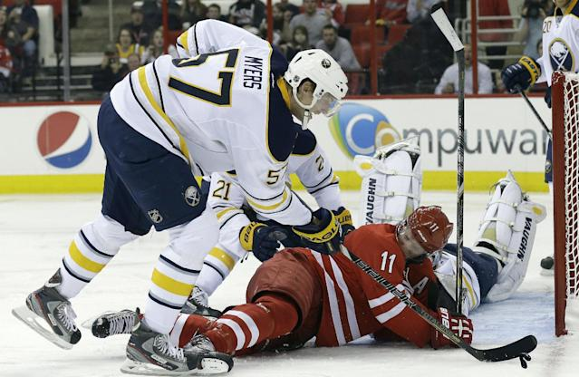 Carolina Hurricanes' Jordan Staal (11) loses his mouthpiece as he tries to score while Buffalo Sabres' Tyler Myers (57) defends during the second period of an NHL preseason hockey game on Friday, Sept. 27, 2013, in Raleigh, N.C. (AP Photo/Gerry Broome)