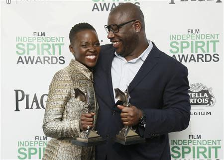 """Actress Nyong'o and director McQueen pose with their awards for """"12 Years a Slave"""" backstage at the 2014 Film Independent Spirit Awards in Santa Monica"""