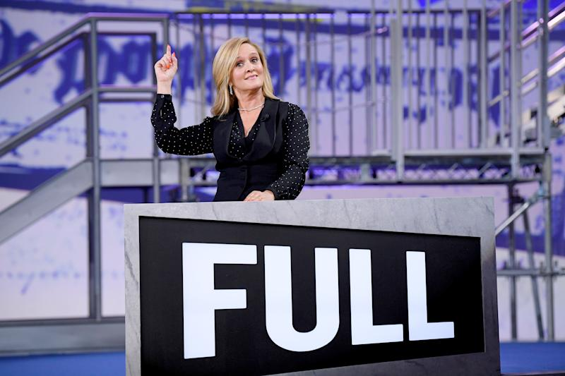Samantha Bee looks gorgeous on stage with her right hand suspended in the air.
