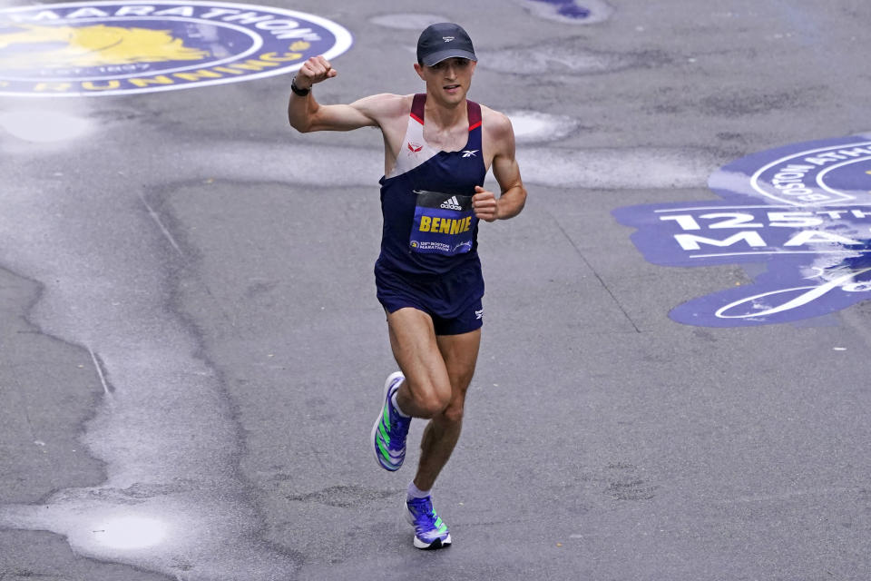 Colin Bennie, of the United States, raises his fist as he approaches the finish line at the Boston Marathon in Boston, Monday, Oct. 11, 2021. Bennie finished seventh. (AP Photo/Charles Krupa)