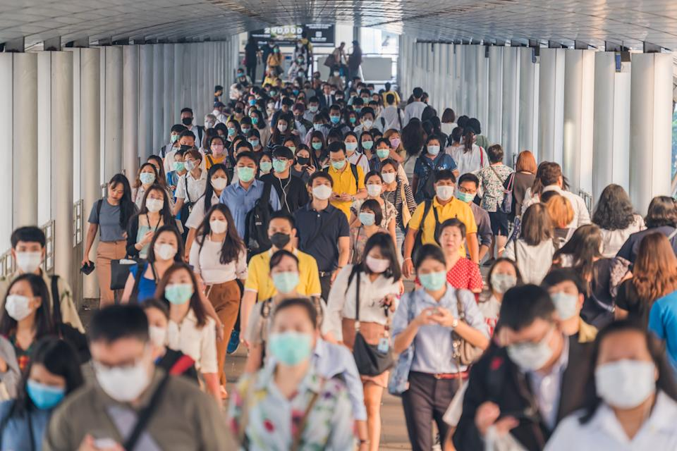 crowds of Asian people wearing face protection while going to their workplace in Bangkok at morning rush hour. wear medical face mask to protect from infection of viruses, pandemic, outbreak and epidemic of disease in crowded