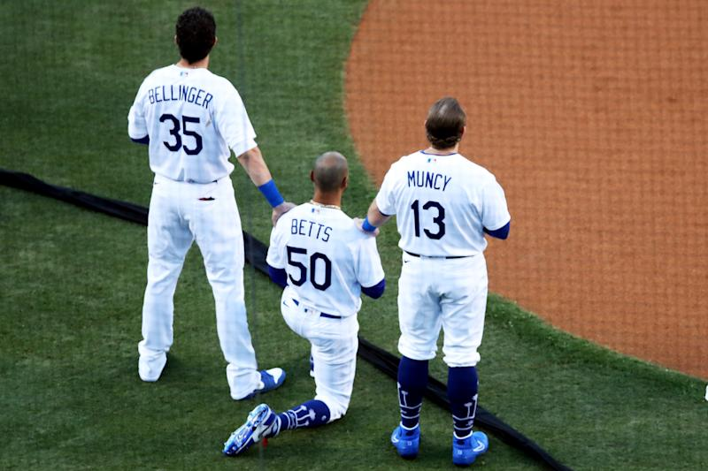 LOS ANGELES, CA - JULY 23: Mookie Betts #50 of the Los Angeles Dodgers kneels during the national anthem as teammates Cody Bellinger #35 and Max Muncy #13 place their hands on his should in support prior to the game between the San Francisco Giants and the Los Angeles Dodgers at Dodger Stadium on Thursday, July 23, 2020 in Los Angeles, California. (Photo by Rob Leiter/MLB Photos via Getty Images)