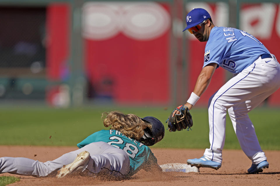 Seattle Mariners' Jake Fraley (28) is forced out at second by Kansas City Royals second baseman Whit Merrifield (15) to get the second out of a double play hit into by Jake Bauers during the fifth inning of a baseball game Sunday, Sept. 19, 2021, in Kansas City, Mo. (AP Photo/Charlie Riedel)