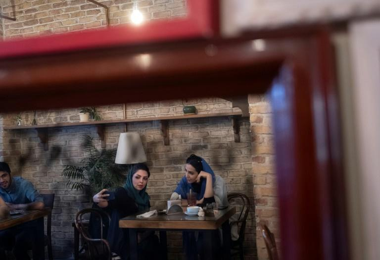 Two Iranian women take a selfie while sitting at a cafe in Tehran on June 14, 2021