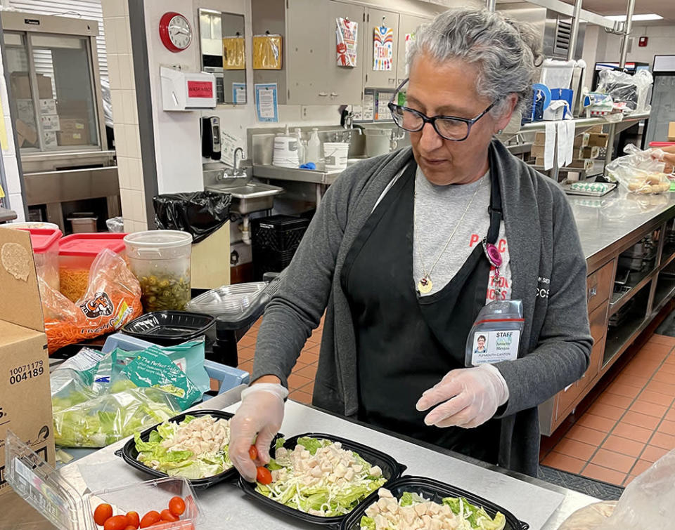 Annette Blevins, who works in nutrition services for Plymouth-Canton Community Schools, finished up chicken caesar salads at Salem High for students in summer school. (Plymouth-Canton Community Schools)