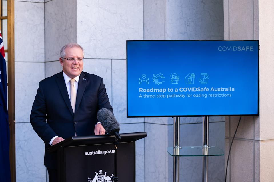 """Prime Minister Scott Morrison has outline a new plan agreed to by the National Cabinet to start easing restrictions imposed in response to the COVID-19 pandemic. The three-step plan aims to deliver a """"COVID-19 safe economy"""". Source: Getty"""