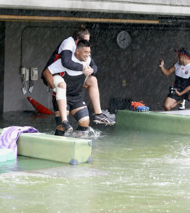 Japan's rugby team player Jiwon Koo, carries teammate James Moore in a flooded walkway at a stadium in Tokyo as the team practices ahead of their match against Scotland, Saturday, Oct. 12, 2019. Tokyo and surrounding areas braced for a powerful typhoon forecast as the worst in six decades, with streets and trains stations unusually quiet Saturday as rain poured over the city. (Yuki Sato/Kyodo News via AP)