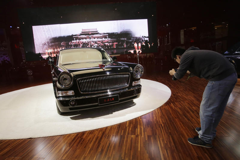 In this April 21, 2013 photo, a visitor takes a close-up photo of Hongqi L9 is displayed at the Shanghai International Automobile Industry Exhibition (AUTO Shanghai) in Shanghai, China. China is reviving the illustrious Red Flag marque, better known at home by its Chinese name, Hong Qi, courtesy of a government-backed program to promote domestic brands that dovetails neatly with efforts to step-up China's diplomatic profile, partly through a greater emphasis on the pomp and circumstance accompanying state visits. The L9, is reserved for Chinese state leaders, flaunts a 6.4-meter (21-foot) armored chassis, suicide doors that open backward, and a price tag reported at around $1 million. (AP Photo/Eugene Hoshiko)