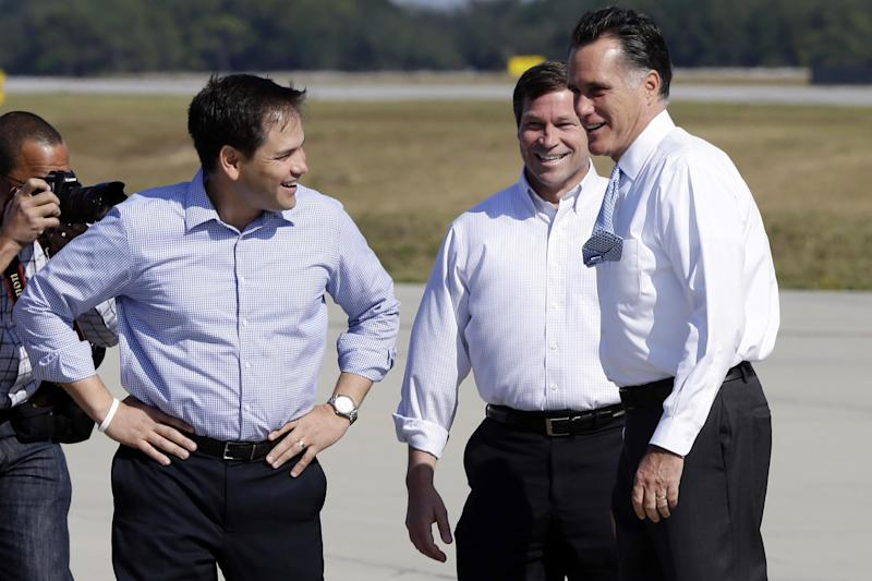Republican presidential candidate and former Massachusetts Gov. Mitt Romney is greeted by Rep. Connie Mack, R-Fla., and Sen. Marco Rubio, R-Fla., left, as he steps off his plane to attend campaign events in Pensacola, Fla., Saturday, Oct. 27, 2012. (AP Photo/Charles Dharapak)