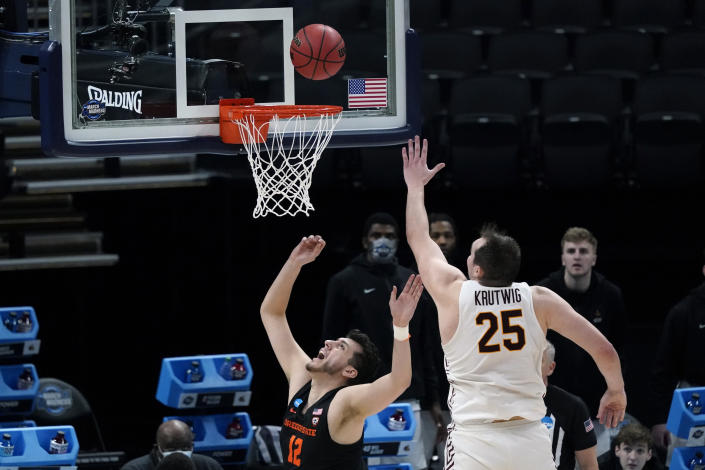 Oregon State center Roman Silva (12) drives to the basket ahead of Loyola Chicago center Cameron Krutwig (25) during the first half of a Sweet 16 game in the NCAA men's college basketball tournament at Bankers Life Fieldhouse, Saturday, March 27, 2021, in Indianapolis. (AP Photo/Jeff Roberson)