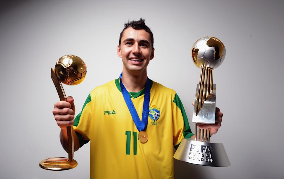 BANGKOK, THAILAND - NOVEMBER 18:  Neto of Brazil poses with the trophies in the locker room after winning the FIFA Futsal World Cup Final at Indoor Stadium Huamark on November 18, 2012 in Bangkok, Thailand.  (Photo by Lars Baron - FIFA/FIFA via Getty Images)