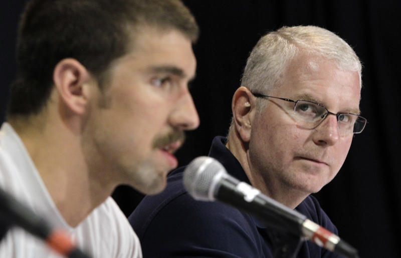 Michael Phelps' coach Bob Bowman, right, looks as Phelps speaks during a news conference at the U.S. Olympic swimming trials, Saturday, June 23, 2012, in Omaha, Neb. The trials starts on Monday. (AP Photo/Mark Humphrey)