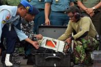 The flight data recorder of AirAsia QZ8501 is lifted out of a carrying case at the airbase in Pangkalan Bun, Central Kalimantan January 12, 2015. REUTERS/Adek Berry/Pool