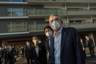 "IOC President Thomas Bach wearing a protective mask visits the Olympic and Paralympic Village in Tokyo Tuesday, Nov. 17, 2020. Bach said during this week's trip to Tokyo that he is ""encouraging"" all Olympic ""participants"" and fans to be vaccinated - if one becomes available - if they are going to attend next year's Tokyo Olympics. (Nicolas Datiche/Pool Photo via AP)"