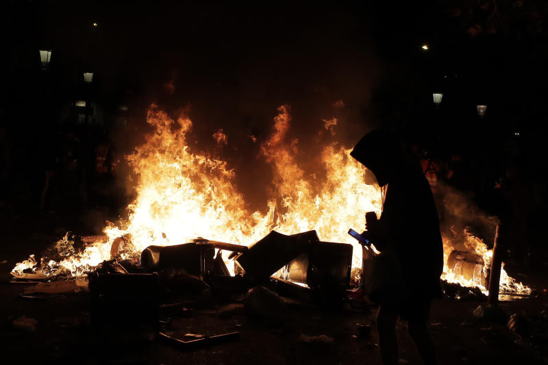 A protester looks at a cell phone by a burning trash container that was set on fire in Barcelona, Spain, Thursday, Oct. 17, 2019. Catalonia's separatist leader vowed Thursday to hold a new vote to secede from Spain in less than two years as the embattled northeastern region grapples with a wave of violence that has tarnished a movement proud of its peaceful activism. (AP Photo/Manu Fernandez)