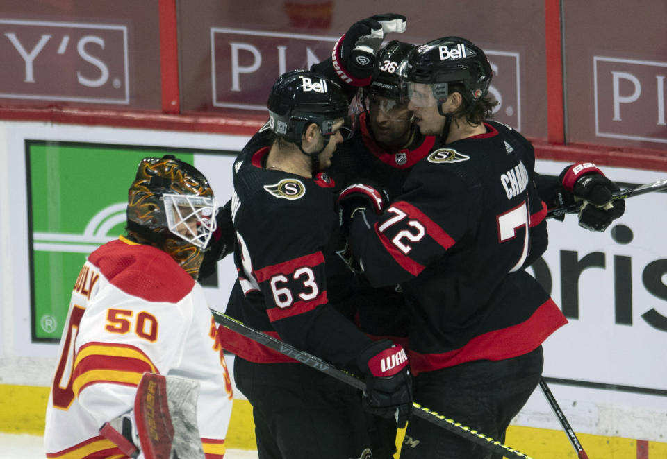 Calgary Flames goalie Artyom Zagidulin looks on as Ottawa Senators center Colin White celebrates his second goal of the game with Ottawa Senators right wing Evgenii Dadonov (63) and defenseman Thomas Chabot (72) during the third period of an NHL hockey game Thursday, Feb. 25, 2021, in Ottawa, Ontario. (Adrian Wyld/The Canadian Press via AP)