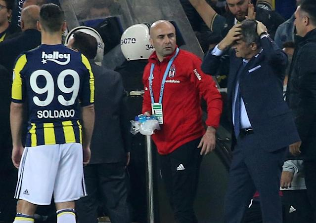 Hospitalised: Besiktas coach Senol Gunes holds his head after being hit by an object thrown during the Turkish Cup semi-final against Fenerbahce (AFP Photo/STRINGER)