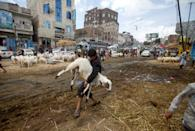 A man carries a sheep at a livestock market ahead of the Eid al-Adha festival amid the coronavirus disease (COVID-19) pandemic in Sanaa, Yemen July 28, 2020. Picture taken July 28, 2020. REUTERS/Mohamed al-Sayaghi TPX IMAGES OF THE DAY