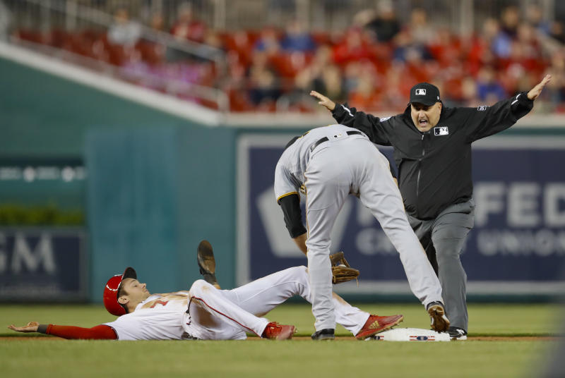 FILE - In this April 30, 2018, file photo, umpire Eric Cooper, right, calls Washington Nationals' Trea Turner, safe at second ahead of the tag by Pittsburgh Pirates shortstop Jordy Mercer, center, during the seventh inning of a baseball game at Nationals Park in Washington. Cooper, the Major League Baseball umpire who worked the AL Division Series two weeks ago, has died. He was 52. Commissioner Rob Manfred announced Cooper's death Sunday, Oct. 20. Cooper died after having a blood clot. (AP Photo/Pablo Martinez Monsivais)