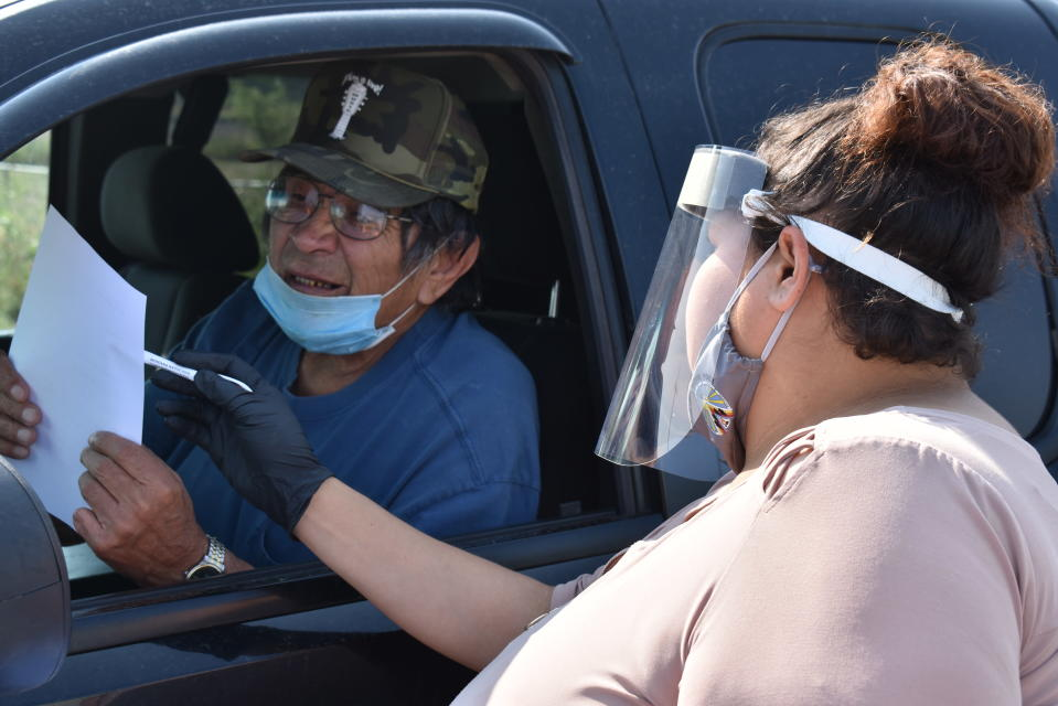 Selena Rides Horse speaks with Gerald Pease at a drive-thru station set up by Western Native Voice to help members of the Crow Indian Tribe participate in the U.S. Census in Lodge Grass, Mont. on Wednesday, Aug. 26, 2020. With millions of federal dollars for impoverished Native American communities on the line in the U.S. census tribes are racing to avoid being undercounted again. (AP Photo/Matthew Brown)