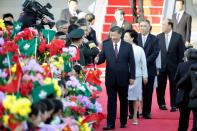 Chinese President Xi Jinping and his wife Peng Liyuan greet officials upon arriving at Macau International Airport in Macau