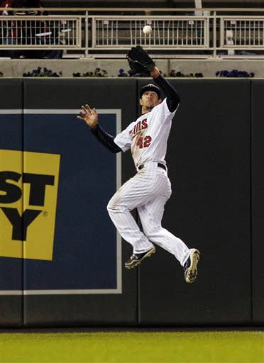 Minnesota Twins left fielder Darin Mastroianni, wearing number 42 in honor of Jackie Robinson Day, makes a leaping catch against the Los Angeles Angels during the ninth inning of a baseball game Monday, April 15, 2013, in Minneapolis. The Twins won 8-2. (AP Photo/Genevieve Ross)