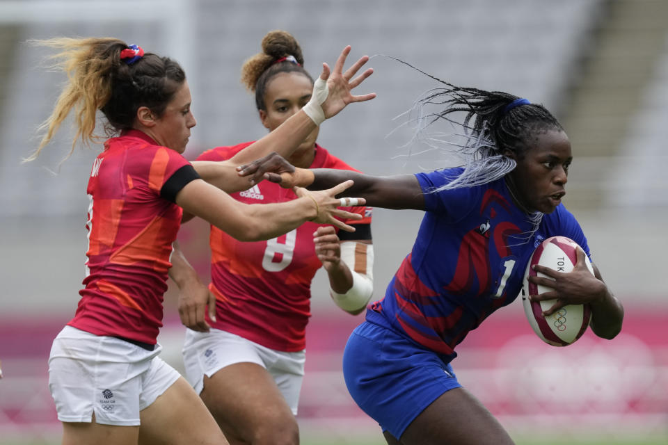 France's Seraphine Okemba runs with the ball, pursued by Britain's Abbie Brown, left, and Celia Quansah, obscured, in their women's rugby sevens semifinal match at the 2020 Summer Olympics, Saturday, July 31, 2021 in Tokyo, Japan. (AP Photo/Shuji Kajiyama)