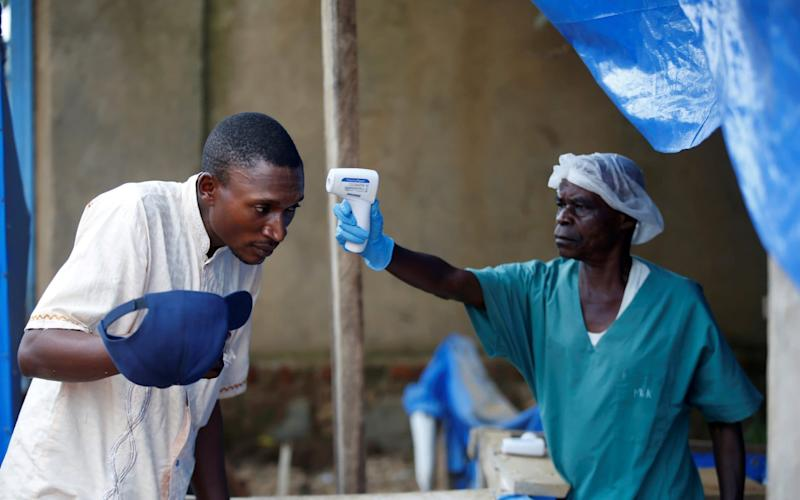 A health worker takes the temperature of a man entering an Ebola treatment centre - REUTERS