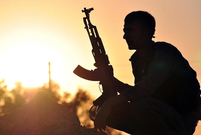 A Kurdish fighter guards a checkpoint near the Syrian town of Ain Issi, on July 10, 2015 (AFP Photo/Delil Souleiman)