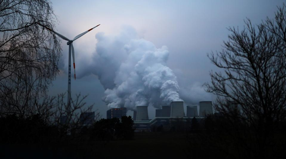 FILE PHOTO: Water vapour rises from the cooling towers of the Jaenschwalde lignite-fired power plant of Lausitz Energie Bergbau AG (LEAG) beside a wind turbine in Jaenschwalde