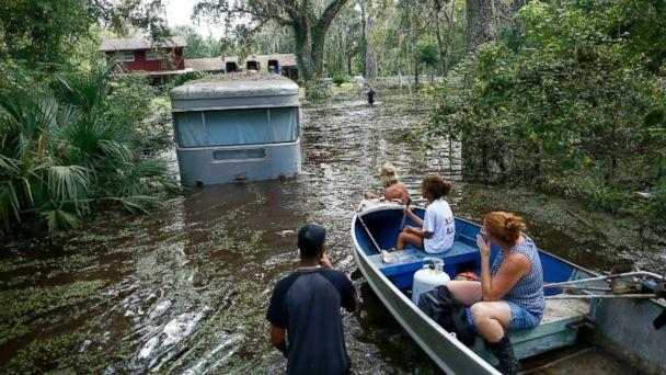 PHOTO: Family members ride in a small boat as Tony Holt's trailer is pulled out of the flood waters from Hurricane Irma in Gainesville, Florida, Sept. 14, 2017, after Hurricane Irma. (Brad McClenny/The Gainesville Sun via AP)