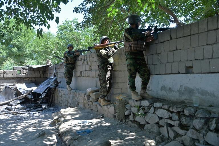 Members of Afghan security forces take positions during clashes with Taliban forces in Mihtarlam
