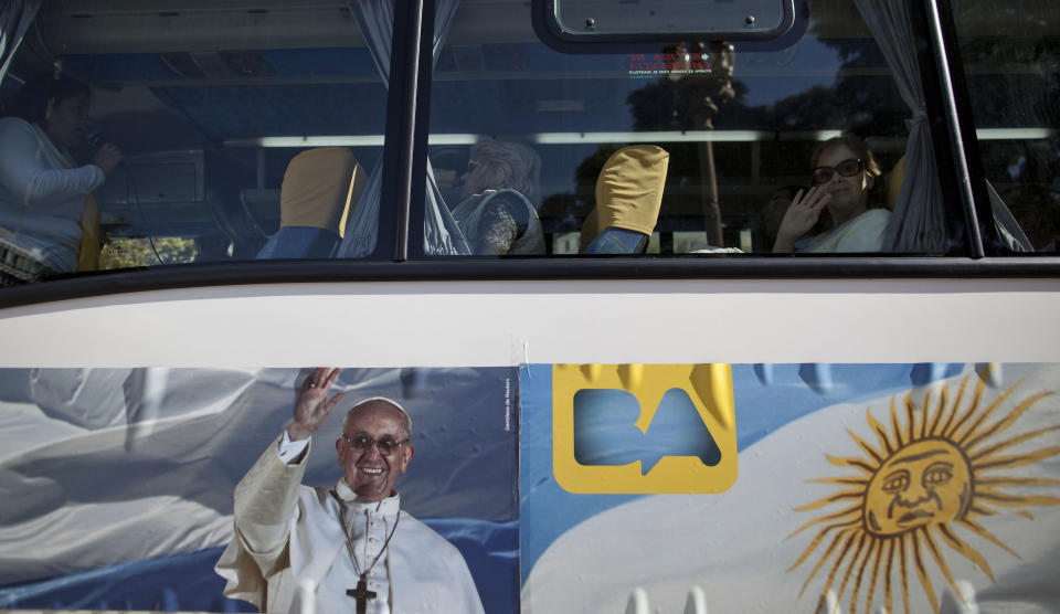 In this May 11, 2013 photo, passengers sit in the single-story cruiser tour bus decorated with a banner of Pope Francis and the Argentine flag in Buenos Aires, Argentina. With an Argentine on the throne of St. Peter, the South American country's capital city has launched a series of guided tours. Three-hour weekend bus trips and walking tours are so far non-commercial in the first step at papal tourism. The bus tours wind through Buenos Aires twice each Saturday and Sunday and can carry about 40 passengers, cruising past 24 sites linked to the new pope. There's no charge for the trip, or for more limited walking tours of downtown and neighborhood sites Tuesdays and Thursdays. (AP Photo/Natacha Pisarenko)
