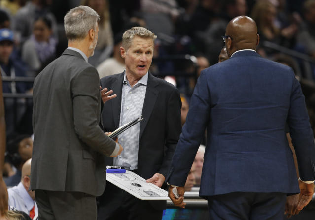 Golden State Warriors head coach Steve Kerr, center, huddles with his assistant coaches during a timeout in the first quarter of an NBA basketball game against the Sacramento Kings in Sacramento, Calif., Monday, Jan. 6, 2020. Kerr was ejected from the game during the second quarter. (AP Photo/Rich Pedroncelli)